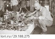 Купить «mature man looking for vintage goods at flea market», фото № 29188275, снято 23 октября 2017 г. (c) Яков Филимонов / Фотобанк Лори