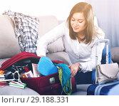 Купить «Girl starting packing luggage for journey at home», фото № 29188331, снято 22 марта 2017 г. (c) Яков Филимонов / Фотобанк Лори