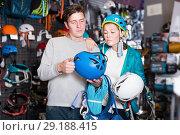 Купить «Young couple in sports shop chooses helmet», фото № 29188415, снято 25 октября 2017 г. (c) Яков Филимонов / Фотобанк Лори
