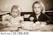 Купить «Two little girls enjoying pastry with cream», фото № 29188439, снято 14 декабря 2018 г. (c) Яков Филимонов / Фотобанк Лори