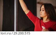 Sexy girl in red dress. The girl spraying water on the pole and wiping it. Стоковое видео, видеограф Константин Шишкин / Фотобанк Лори