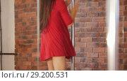 Sexy girl in red dress training pole dancing. Стоковое видео, видеограф Константин Шишкин / Фотобанк Лори