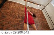 Sexy girl in red dress training pole dancing. Jumping on the pole. Стоковое видео, видеограф Константин Шишкин / Фотобанк Лори