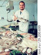 Купить «Positive salesman in black glove holding fish», фото № 29200699, снято 27 октября 2016 г. (c) Яков Филимонов / Фотобанк Лори