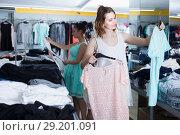 Купить «Cheerful female customer selecting new garments», фото № 29201091, снято 19 июня 2017 г. (c) Яков Филимонов / Фотобанк Лори