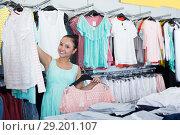 Купить «Smiling young woman shopper choosing new garments», фото № 29201107, снято 19 июня 2017 г. (c) Яков Филимонов / Фотобанк Лори