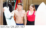 Купить «Young couple planning to surf, choosing boards and surfing suits in beach club», фото № 29201167, снято 30 апреля 2018 г. (c) Яков Филимонов / Фотобанк Лори