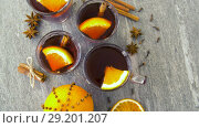 Купить «glasses of hot mulled wine with orange and spices», видеоролик № 29201207, снято 7 октября 2018 г. (c) Syda Productions / Фотобанк Лори