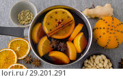 Купить «pot with hot mulled wine, orange slices and spices», видеоролик № 29201291, снято 7 октября 2018 г. (c) Syda Productions / Фотобанк Лори