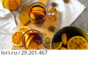 Купить «glasses of hot mulled wine with orange and spices», видеоролик № 29201467, снято 7 октября 2018 г. (c) Syda Productions / Фотобанк Лори