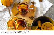 Купить «glasses of hot mulled wine with orange and spices», видеоролик № 29201467, снято 7 октября 2018 г. (c) Syda Productions / Фотобанк Лори