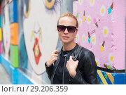 Купить «Woman talking on smartphone leaning against colorful graffiti wall in New York city, USA.», фото № 29206359, снято 4 апреля 2020 г. (c) Matej Kastelic / Фотобанк Лори
