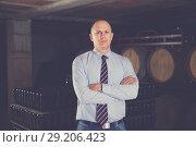 Купить «Confident succesful man winemaker posing in own winery vault», фото № 29206423, снято 22 января 2018 г. (c) Яков Филимонов / Фотобанк Лори