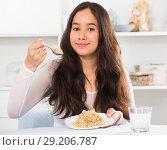 Купить «Positive young female eating cereals», фото № 29206787, снято 30 мая 2017 г. (c) Яков Филимонов / Фотобанк Лори