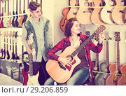 Купить «Young rock-n-roll players are choosing between acoustic and electric guitar», фото № 29206859, снято 14 февраля 2017 г. (c) Яков Филимонов / Фотобанк Лори