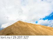 Купить «A large mountain of sand against a cloudy sky», фото № 29207327, снято 27 сентября 2018 г. (c) Валерий Смирнов / Фотобанк Лори