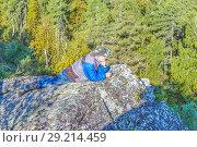 Купить «An elderly tourist man lies on a rock against the backdrop of the endless Forest Valley.», фото № 29214459, снято 6 сентября 2017 г. (c) Акиньшин Владимир / Фотобанк Лори
