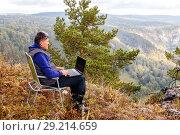 Купить «Mature male tourist is working on a laptop on top of the High Mountain.», фото № 29214659, снято 9 сентября 2017 г. (c) Акиньшин Владимир / Фотобанк Лори