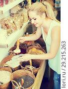 Купить «young woman picking dried beans in store», фото № 29215263, снято 14 ноября 2018 г. (c) Яков Филимонов / Фотобанк Лори