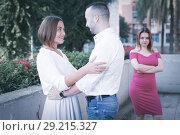 Купить «Cheerful couple are talking and woman is envying them», фото № 29215327, снято 18 октября 2017 г. (c) Яков Филимонов / Фотобанк Лори