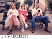 Купить «Young people are focusing on smartphones during a together walking outdoors.», фото № 29215331, снято 18 октября 2017 г. (c) Яков Филимонов / Фотобанк Лори