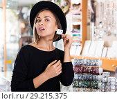 Купить «Woman customer in hat trying earrings», фото № 29215375, снято 16 октября 2017 г. (c) Яков Филимонов / Фотобанк Лори