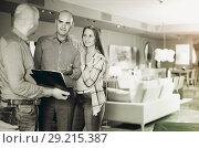 Купить «Adult salesman showing customers product catalog», фото № 29215387, снято 16 мая 2017 г. (c) Яков Филимонов / Фотобанк Лори