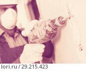 Купить «Worker renovating with drill in gloves and mask», фото № 29215423, снято 18 мая 2017 г. (c) Яков Филимонов / Фотобанк Лори