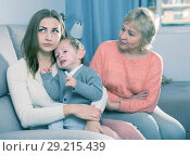 Купить «Adult female with her mother are having disagreements for parenting child», фото № 29215439, снято 15 февраля 2018 г. (c) Яков Филимонов / Фотобанк Лори