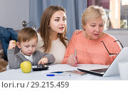 Купить «Woman is talking her mother how to fill utility bills with laptop», фото № 29215459, снято 15 февраля 2018 г. (c) Яков Филимонов / Фотобанк Лори