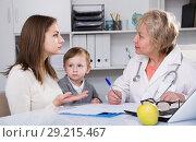Купить «Pediatrist woman is examining kid and talking to his puzzled mother about it», фото № 29215467, снято 15 февраля 2018 г. (c) Яков Филимонов / Фотобанк Лори