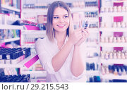 Купить «Portrait of girl with colored eyeliners in hand in store», фото № 29215543, снято 31 января 2018 г. (c) Яков Филимонов / Фотобанк Лори