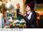 Купить «Woman choosing Christmas decoration at market», фото № 29215627, снято 22 декабря 2016 г. (c) Яков Филимонов / Фотобанк Лори