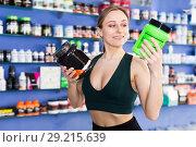Купить «Young woman reading label before buying», фото № 29215639, снято 12 апреля 2018 г. (c) Яков Филимонов / Фотобанк Лори