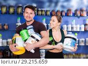 Купить «Happy young sporty people standing in store, holding big can of sport nutrition», фото № 29215659, снято 12 апреля 2018 г. (c) Яков Филимонов / Фотобанк Лори