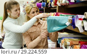 Portrait of two positive attractive girls choosing fabric among diversity on shelves in store. Стоковое видео, видеограф Яков Филимонов / Фотобанк Лори
