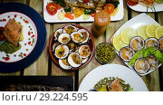 Купить «Top view of dishes from trout and mollusks served on wooden background», видеоролик № 29224595, снято 17 сентября 2018 г. (c) Яков Филимонов / Фотобанк Лори