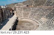 Купить «The ruins of old city debris of Turkish amphitheater. Archaeological Attraction. Ancient city Hierapolis near Marmaris in Turkey», видеоролик № 29231423, снято 20 октября 2018 г. (c) Сергей Тимофеев / Фотобанк Лори