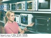 Купить «Positive female looking new microwave for kitchen in furniture store», фото № 29231555, снято 1 марта 2018 г. (c) Яков Филимонов / Фотобанк Лори