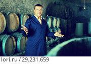 Купить «Smiling man wine technician working in storage», фото № 29231659, снято 22 сентября 2016 г. (c) Яков Филимонов / Фотобанк Лори