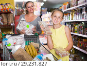 Купить «Mom and the girl show their favorite foods in the supermarket», фото № 29231827, снято 5 июня 2017 г. (c) Яков Филимонов / Фотобанк Лори