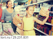 Купить «Girl 10-12 years old is showing purchases which they chosen with mother», фото № 29231831, снято 5 июня 2017 г. (c) Яков Филимонов / Фотобанк Лори
