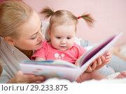 Купить «Mommy reads baby book», фото № 29233875, снято 16 октября 2018 г. (c) Оксана Кузьмина / Фотобанк Лори