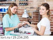 Купить «Woman polishing nails to female client in modern beauty salon», фото № 29234295, снято 30 мая 2018 г. (c) Яков Филимонов / Фотобанк Лори