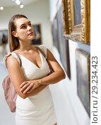 Купить «Woman visiting painting exhibition», фото № 29234423, снято 28 июля 2018 г. (c) Яков Филимонов / Фотобанк Лори
