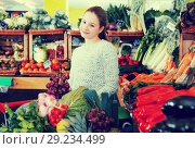 Купить «Happy girl among fruits and vegetables on store shelves», фото № 29234499, снято 13 февраля 2018 г. (c) Яков Филимонов / Фотобанк Лори