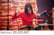 Купить «Repetition. Girl in red sweater passionately plays the drums», видеоролик № 29235007, снято 8 июля 2020 г. (c) Константин Шишкин / Фотобанк Лори