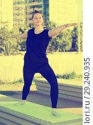 Купить «Young woman doing exercises outdoors», фото № 29240935, снято 5 июля 2017 г. (c) Яков Филимонов / Фотобанк Лори