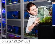 Купить «Woman looks at the aquarium with small fish», фото № 29241031, снято 17 февраля 2017 г. (c) Яков Филимонов / Фотобанк Лори