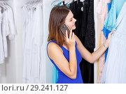 Купить «Girl choosing dress and talking on phone», фото № 29241127, снято 17 сентября 2018 г. (c) Яков Филимонов / Фотобанк Лори